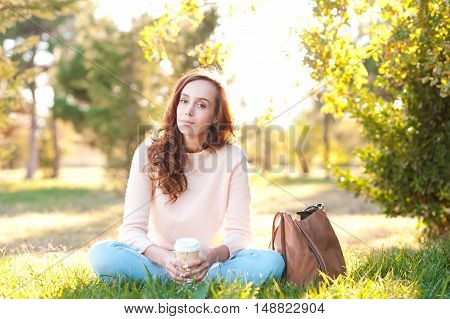 Beautiful girl 20-24 year old wearing casual clothes holding cup of coffee outdoors. Sitting on green grass in park.