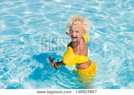 Happy laughing little boy playing in outdoor swimming pool on a hot summer day. Kids learn to swim. Child with colorful armbands. Family vacation in tropical resort.
