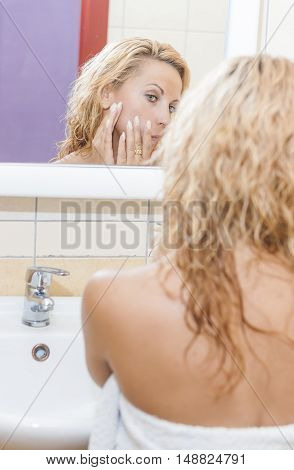 Health Concept and Ideas. Portrait of Caucasian Woman in Bathroom Checking Her Acnes Prone Skin in Mirror Reflection. Vertical Image Orientation