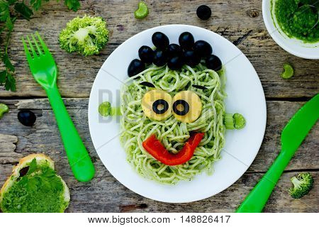 Creative idea for baby dinner or lunch - green spaghetti monster with broccoli parsley celery black olives and pepper. Concept of funny and healthy meal food for children top view