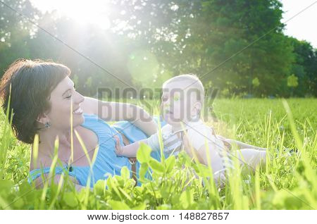Happy Family Life Concepts and Ideas. Caucasian Brunette Mother with Her Toddler Son Spending Time Together Outdoors Embraced in Park. Horizontal Image