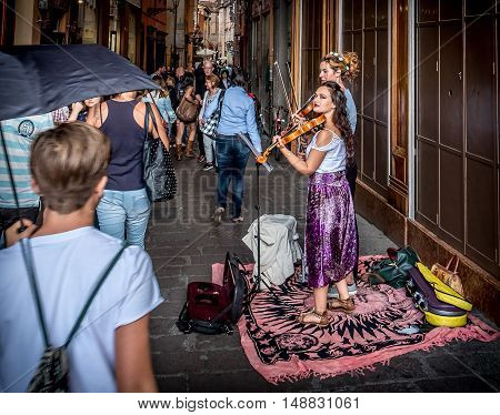 Bologna Italy 18 September 2016: two buskers violinists perform for the passersby in the historic district of Bologna.