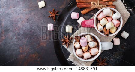 Hot chocolate with marshmallows and spices on grunge dark table. Selective focus, tasty holidays concept. Drink for fall and winter. Copy space background, top view overhead flat lay