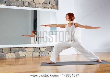 Yoga Warrior two II pose exercise in wooden floor gym and mirror indoor