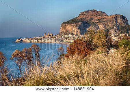 Landscape View on the coastal city of Cefalu on Sicily in Italy in the evening. Blue sky and sea. Large rock and medieval tourist town with old cathedral