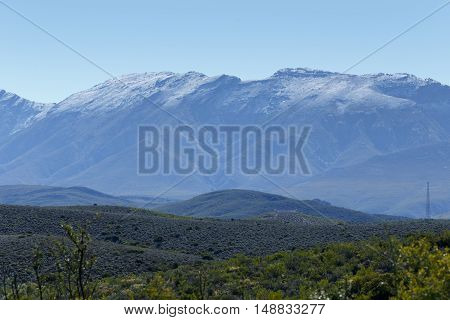 One Tiny Tower On A  Green Landscape With Silver Snow Filled Mountain Range In De Rust