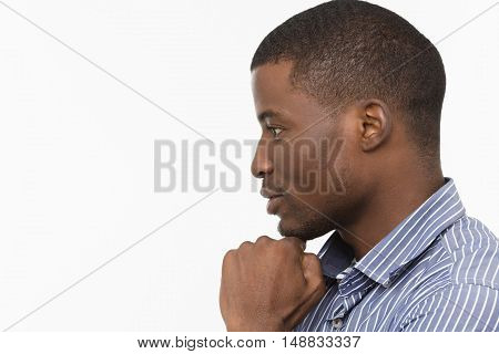 Closeup profile of handsome Afro-American man looking somewhere while posing for photographer isolated on white background in studio.