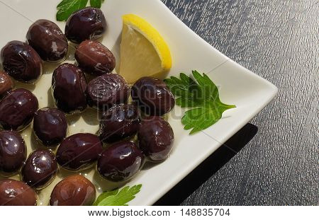 Black olives in a white plate with olive oil