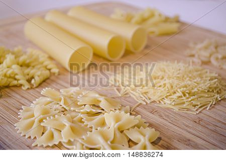 the Italian food - heap of macaroni, spaghetti, noodles, pasta and cannelloni tubes - selective soft focus