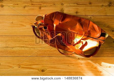Vintage orange unisex leather bag on the wooden floor (view from above)