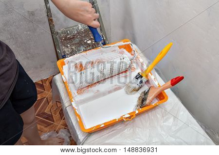 Paints tray with whaite paint and tools used for painting construction paintbrushes and paint rollers.