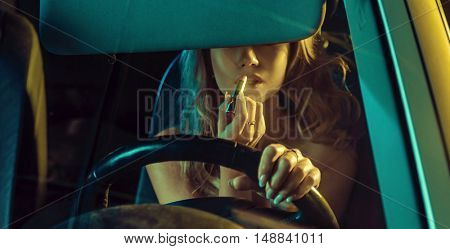 Attractive blonde beauty using lipstick in a car