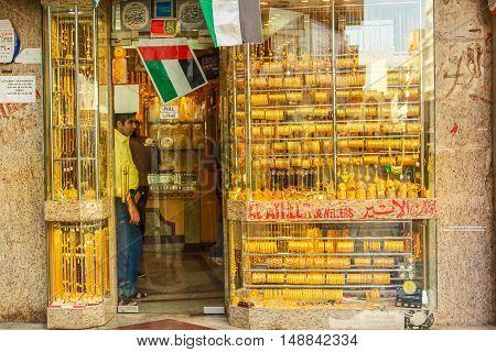 Dubai, UAE - May 3, 2013: jewelers in a typical gold shop in Old Deira. The Grand Souk Deira is an entire neighborhood of narrow streets and dark and bottege selling spices, gold, perfumes.