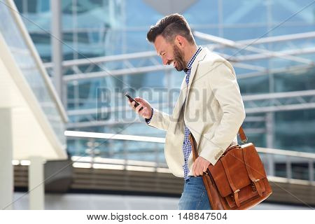 Smiling Mature Man With Bag Using Cell Phone