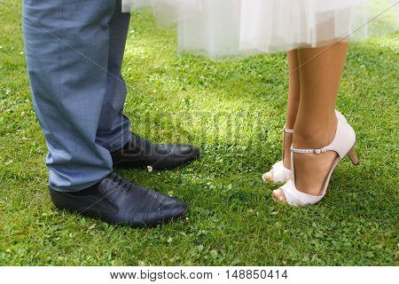 Close-up of bride's and groom's feet standing on green grass