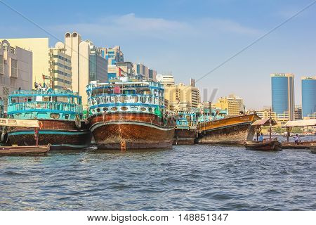 Dubai, United Arab Emirates - May 3, 2013: traditional wooden boats docked on the Bay Creek in United Arab Emirates. On background the skyline of Deira and of Twin Towers, old downtown of Dubai.