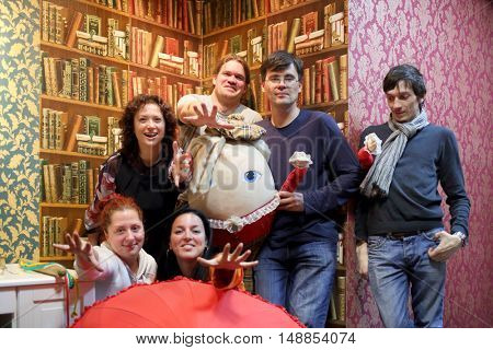 MOSCOW - MAR 17, 2015: Portrait of a group of six funny bloggers near a wall with painted shelves and books in the quest Funlock