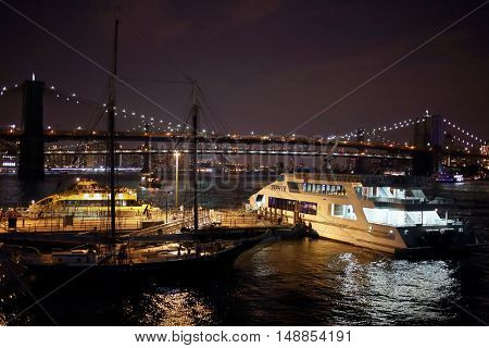 NEW YORK, USA - SEP 07, 2014: Pier with boat and water taxi in front of luminous Night Bridge in New York City