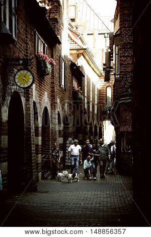 BREMEN, GERMANY - AUGUST 30: Pedestrians with dogs going through the narrow and famous Boettcher Street with shops and stores on August 30, 2016 in Bremen.