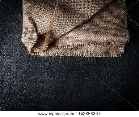 Sackcloth on black stone background. Top view