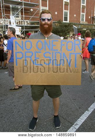 Asheville, North Carolina, USA: September 12, 2016: A young male protester holds a sign at a Donald Trump Rally saying
