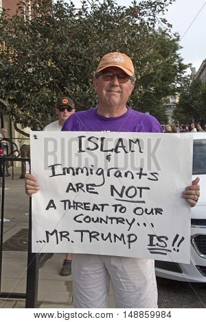 Asheville, North Carolina, USA: September 12, 2016: Middle aged male protester at a Donald Trump campaign rally holds a sign saying that Trump Not Immigrants Are a Threat to Our Country on September 12, 2016 in downtown Asheville, NC