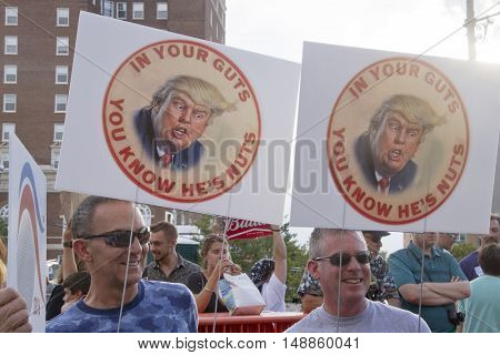 Asheville, North Carolina, USA: September 12, 2016: Protesters hold signs at a Donald Trump Rally saying not tolet him infect our country and in your guts you know he's nuts on September 12, 2016 in downtown Asheville, NC