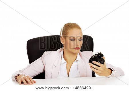Tired business woman sitting behind the desk and holding alarm clock