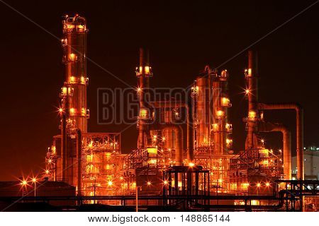 closeup of oil refinery distillation tower at night