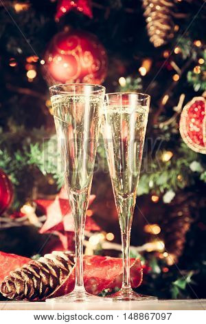 Two Glasses Of Champagne With Christmas Tree Background. Holiday Season Background. Traditional Red