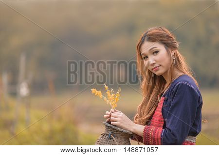 Portrait of Asian longhair young lady in tribe dress sit near swamp.