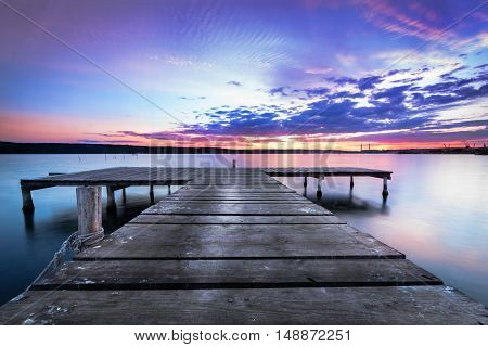 Wooden pier on a blue lake sunset and smooth reflection on water.