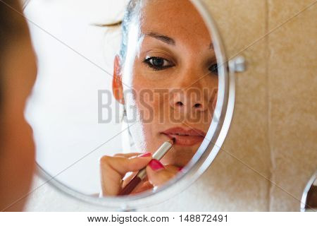 Mirror reflection of beautiful adult woman put on lip pencil