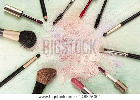 Makeup brushes and lipstick on teal blue background, with traces of powder and blush, forming a frame. Horizontal template for makeup artist's business card or flyer design, with copyspace