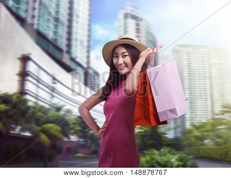 Young Asian Woman With Hat Holding Colored Shopping Bags