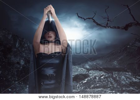 Witch Woman With Black Costume Wearing Cloak And Holding Knife