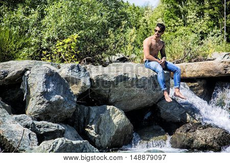 Athletic shirtless young man outdoor at river or water stream, sitting on big rock, looking away, with stones in background
