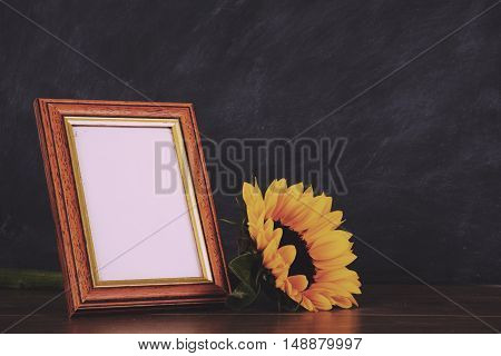 Old picture frame and sunflower against a dirty blackboard background Vintage Retro Filter.