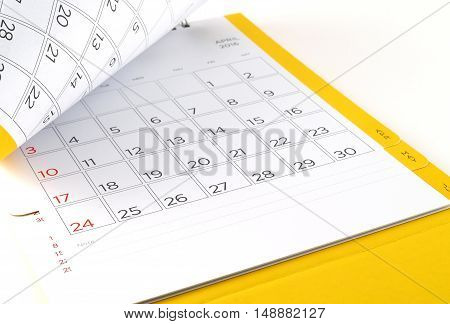 close up cardboard desk calendar with days and dates of April 2016 in grid and blank lines for text notes, reminder monthly business planning or meeting deadline, flip the calendar page