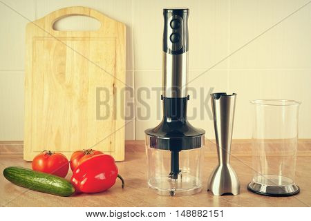Fresh vegetables and a blender on the kitchen table gently toned