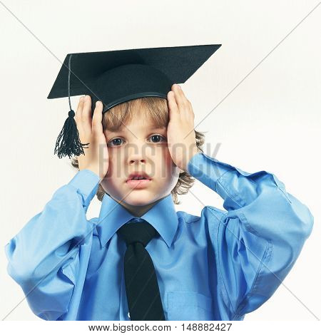 Young tired professor in academic hat on a light background gently toned