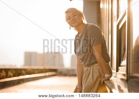 beautiful blonde girl stand against city view in sunny rays at sunset in summer . Alone Cute young adult blond woman enjoy warm evening
