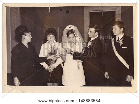 CHUDNOV UKRAINE - CIRCA 1960: Employee of Civil Acts Registration Office carries out solemn ceremony of marriage of bride and groom in presence of witnesses (vintage photo approximately 1960s)
