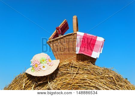 Picnic basket with wine and hat in summer time
