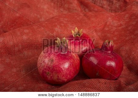 Pomegranates on a red burlap yuta background