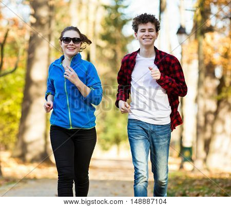 Teenage girl and boy running in city park
