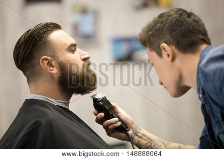 Young Man Getting Beard Grooming At Barbershop