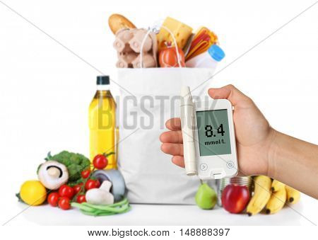 Male hand holding glucometer with bag of fresh products on white background. Diabetes concept