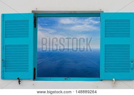 blue window against volcano caldera and Aegan sea, beautiful details of Santorini island, Greece