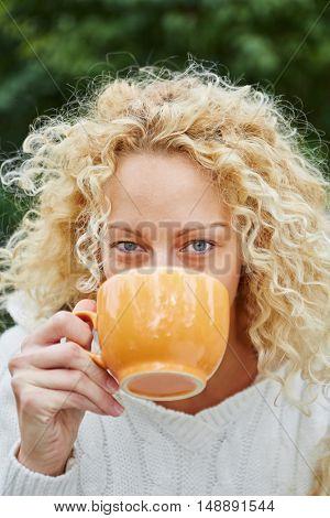 Happy blond woman drinking tea in garden in the fall